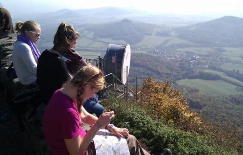 Students map landscape structure from the summit of Milešovka.